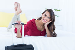 Beautiful woman with a suitcase lying on her bed Royalty Free Stock Photography