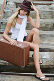 The beautiful woman with a suitcase on an old ladder Stock Photos