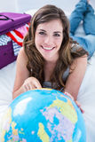 Beautiful woman with a suitcase pointing on a globe Royalty Free Stock Photos