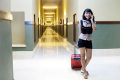 Beautiful woman with suitcase talking on the phone Stock Photo