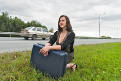 Beautiful woman with suitcase waits on road Royalty Free Stock Images