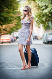 Beautiful woman with suitcases crossing the street in a big city Royalty Free Stock Photos