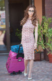 Beautiful woman with suitcases leaving the hotel in a big city. Attractive redhead with sunglasses and elegant dress on street Stock Image