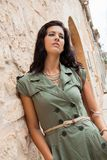 Beautiful woman with a sulky expression. Beautiful brunette woman with a sulky expression leaning against an old stone wall in a narrow street staring at the Stock Image