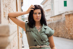 Beautiful woman with a sulky expression. Beautiful brunette woman with a sulky expression leaning against an old stone wall in a narrow street staring at the Royalty Free Stock Images