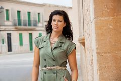 Beautiful woman with a sulky expression. Beautiful brunette woman with a sulky expression leaning against an old stone wall in a narrow street staring at the Stock Photography
