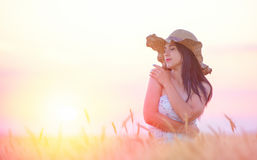 Beautiful woman with summer hat in wheat field at sunset. Time Stock Photography