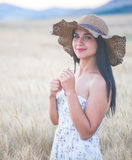Beautiful woman with summer hat in wheat field at sunset. Timne Stock Photos