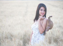 Beautiful woman with summer hat in wheat field at sunset. Time Stock Photo