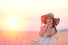 Beautiful woman with summer hat in wheat field at sunset. Time Royalty Free Stock Image