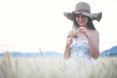 Beautiful woman with summer hat in wheat field at sunset. Time Stock Images