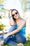 Beautiful woman in summer outfit. Beautiful woman in a summer outfit of denim jeans and a trendy blue top sitting on the grass outdoors wearing sunglasses, high Stock Photography