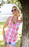 The beautiful woman in the summer standing at a tree Stock Photography