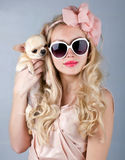 Beautiful woman in sun glasses and small chihuahua in hands Stock Photo
