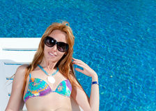 Beautiful woman in sun glasses sunbathes at pool Royalty Free Stock Photography