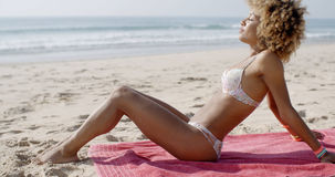 Beautiful Woman Sunbathing On A Beach. African-american beautiful woman sunbathing on a beach on the blanket Royalty Free Stock Photos