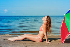 Beautiful woman sunbathing on a beach. Beautiful woman sunbathing on a beach with an umbrella royalty free stock photos
