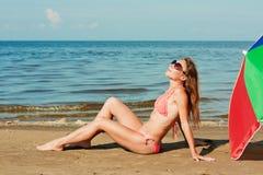 Beautiful woman sunbathing on a beach. Beautiful woman sunbathing on a beach with an umbrella stock photos