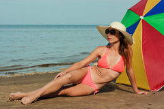 Beautiful woman sunbathing on a beach. Stock Photos