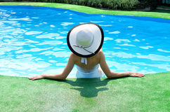 Beautiful woman sunbathing by the pool. Summer background. Young slim woman in hat sitting in swimming pool Stock Images