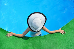 Beautiful woman sunbathing by the pool, top view. Girl with a hat on the edge of a swimming pool, enjoying the sun, water Royalty Free Stock Images