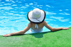 Beautiful woman sunbathing by the pool, top view. Young woman in sun hat in the pool, top view Stock Images