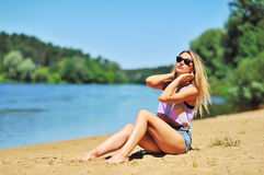 Beautiful woman sunbathing at the riverside Stock Image