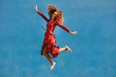 Beautiful woman in sundress jumping with joy stock photo