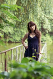 Beautiful woman in sundress on the pond bridge. In the forest Royalty Free Stock Image