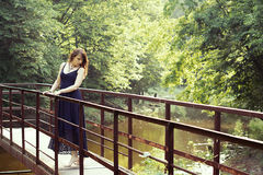Beautiful woman in sundress on the pond bridge. In the forest Stock Photo
