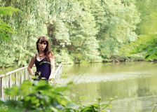 Beautiful woman in sundress on the pond bridge Royalty Free Stock Images