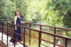 Beautiful woman in sundress on the pond bridge Royalty Free Stock Photography