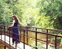Beautiful woman in sundress on the pond bridge Royalty Free Stock Photos