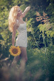 Beautiful woman between sunflower Stock Photo