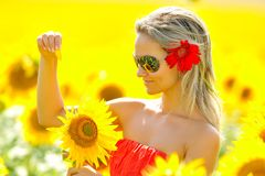 Beautiful woman between sunflowers Stock Photography