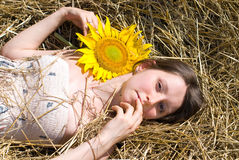 Beautiful Woman with Sunflowers near Haystack - Beauty and Fashion Royalty Free Stock Image