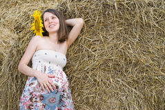 Beautiful Woman with Sunflowers near Haystack - Beauty and Fashion Royalty Free Stock Photos