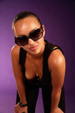 Beautiful woman in sunglasses. Violet background Royalty Free Stock Photo