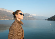 Beautiful woman in sunglasses on a background of lake and mountains. Woman in sunglasses on a background of lake and mountains stock photo