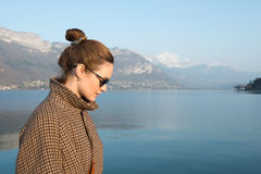 Beautiful woman in sunglasses on a background of lake and mountains. Cute woman on the background of mountain scenery royalty free stock photo