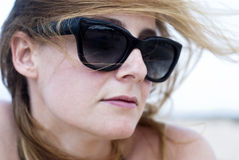 Beautiful woman in sunglasses on a beach. Closeup of beautiful woman in sunglasses on a beach Royalty Free Stock Photos