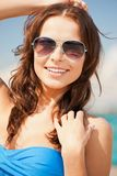 Beautiful woman in sunglasses on a beach. Picture of beautiful woman in sunglasses on a beach Royalty Free Stock Images