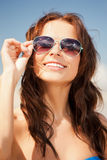 Beautiful woman in sunglasses on a beach. Picture of beautiful woman in sunglasses on a beach Royalty Free Stock Photo