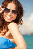 Beautiful woman in sunglasses on a beach. Picture of beautiful woman in sunglasses on a beach Stock Photography