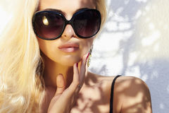 Beautiful woman in sunglasses.beauty blond girl in near the wall. Summer Royalty Free Stock Images