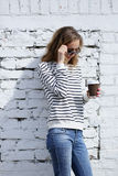 Beautiful woman in sunglasses with a disposable cofee cup Stock Image