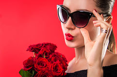 Beautiful woman in sunglasses holding roses Royalty Free Stock Images