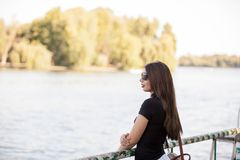 Beautiful woman in sunglasses looking at the river. Relax and nature Stock Photo