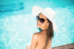 Beautiful woman in sunglasses sitting by pool. On sunny day Stock Photos