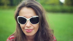 Beautiful woman in sunglasses at the summer park.  stock video footage